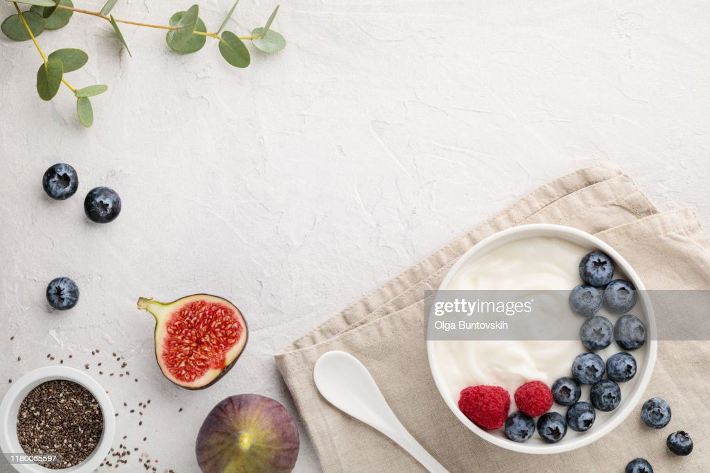 White fermented yogurt with blueberry, figs, chia seeds and raspberry in bowl on light gray table : Stock Photo