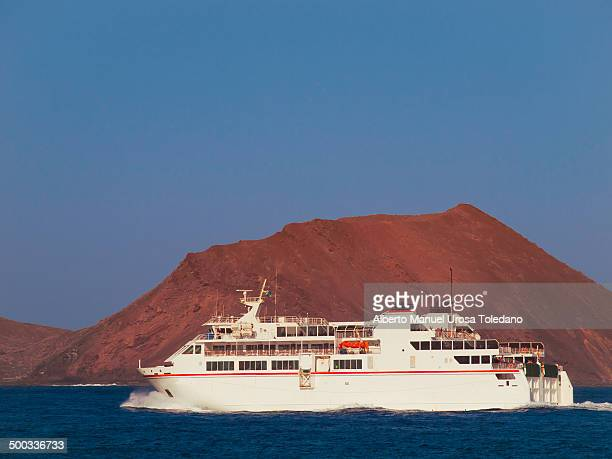 CONTENT] A white ferry going between Corralejo town in Fuerteventura island and Playa Blanca town in Lanzarote island with the Lobos small island in...