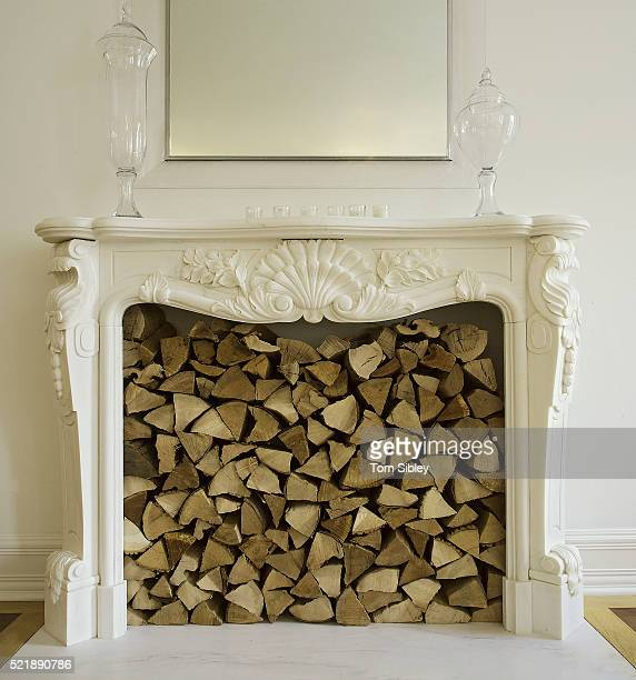 White Fireplace Filled With Stacked Firewood