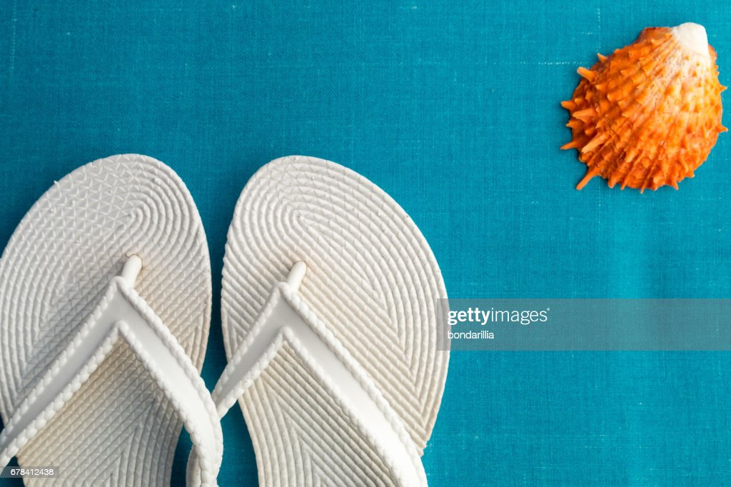 3a0d68e88 White flip flop near seashell on blue background. Top view.   Stock Photo