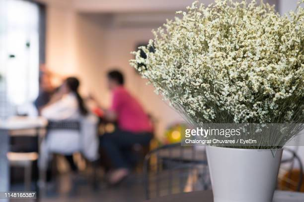 White Flower Vase With People In Background At Cafe