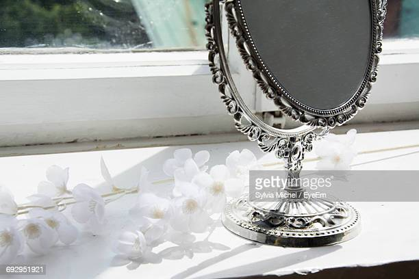 White Flowers By Hand Mirror On Window Sill
