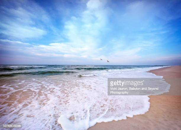 white foam and blue skies at sunrise at jone beach, long island - jones beach stock pictures, royalty-free photos & images