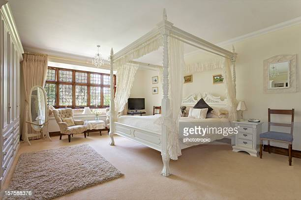 white four-poster bed in large neutral-colored bedroom - erker stockfoto's en -beelden