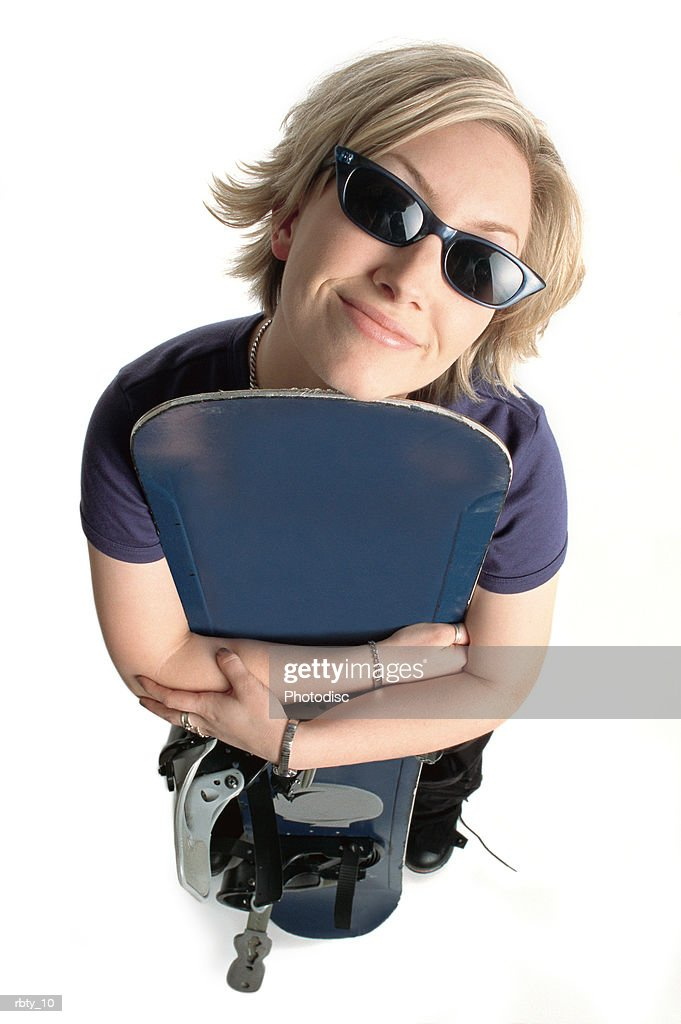 white funky female snowborder with blonde hair and sunglasses looking up at the camera holding her snowboard smiling : Foto de stock