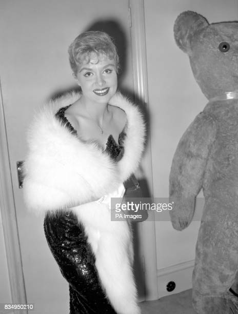 A white fur stole tops the black dress covered with thousands of sequins and ending in a 'mermaid tail' effect at the back worn by singer Yana She...