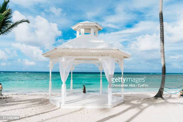 white gazebo at beach against cloudy sky - gazebo stock pictures, royalty-free photos & images