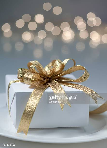 White gift box with gold ribbon and bow with blurred lights