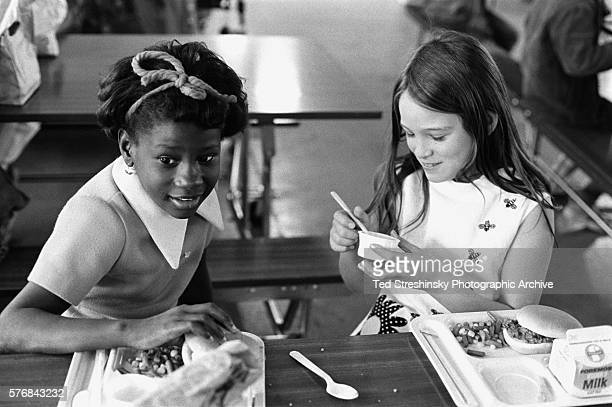 A white girl and an African American girl eat lunch together at a desegregated school in Bekeley California