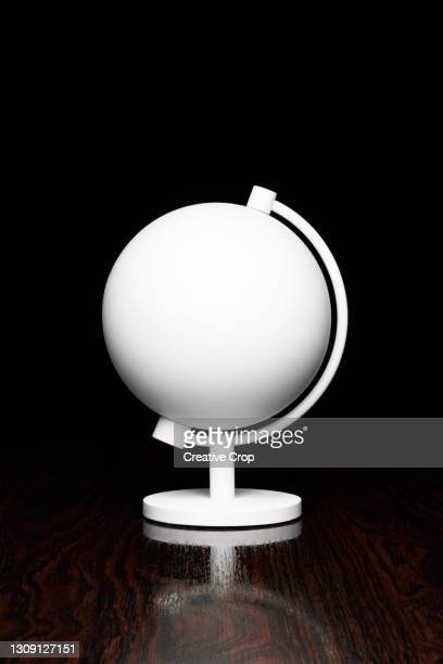 a white globe on a desktop - microzoa stock pictures, royalty-free photos & images