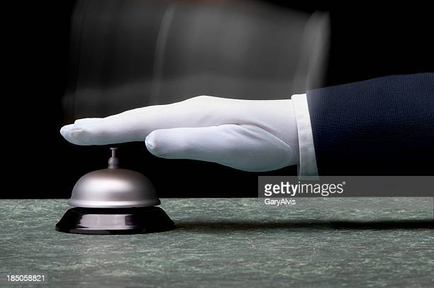 White gloved hand ringing silver service bell on counter.