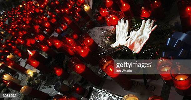 White gloves lie amongst red candles at Atocha train station as a memorial for those killed in the terrorist bombings March 13 2004 in Madrid Ten...