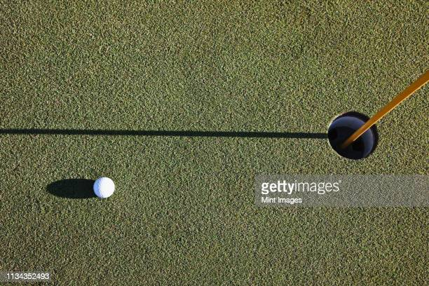 white golf ball near the cup - putting golf stock pictures, royalty-free photos & images