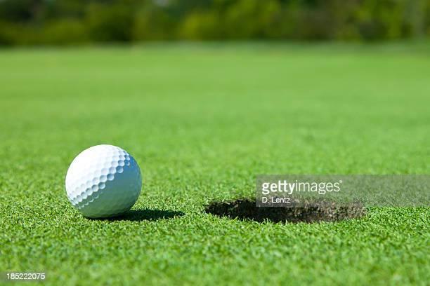 White golf ball stood next to a hole