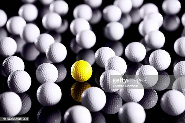 White golf balls with one yellow one