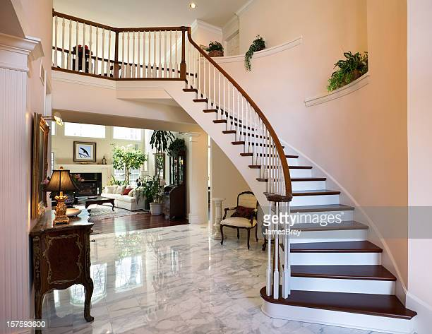 Escalera blanca de gran vestíbulo, piso de mármol reflejan diseño Interior de la casa