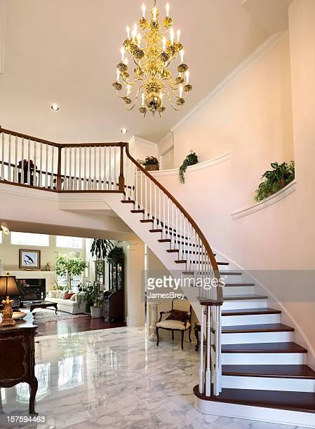 Escalera blanca de gran vestíbulo, piso de mármol reflejan hogar, con Chandelier