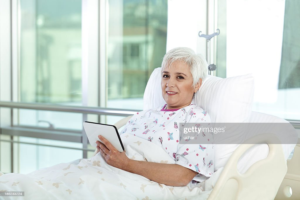 white hair patient in bed using tablet at hospital : Stock Photo