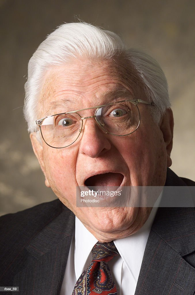 white haired elderly caucasian man in suit wears glasses stares open mouthed with a look of shock : Stockfoto
