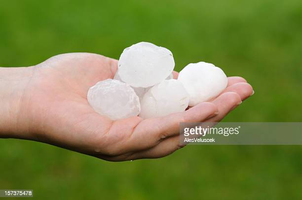 A white hand holding large hailstones on its palm