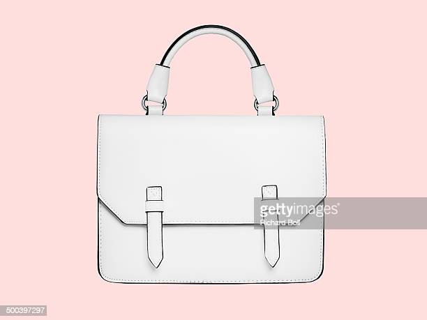 White handbag against a pink background