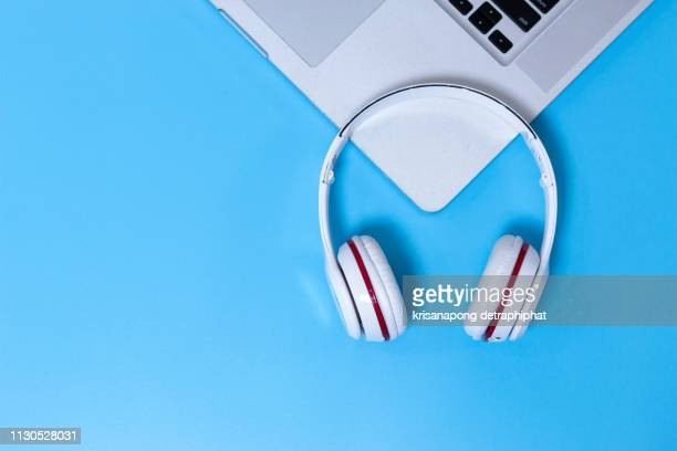 white headphones on a blue background - podcast stock-fotos und bilder