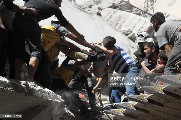 White Helmet rescue volunteers and civilians rescue a child from the rubble of a building destroyed during an air strike by Syrian regime forces and...