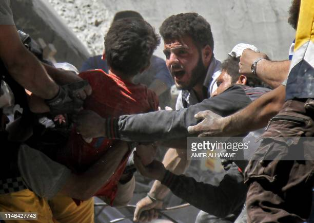 TOPSHOT White Helmet rescue volunteers and civilians rescue a child from the rubble of a building destroyed during an air strike by Syrian regime...
