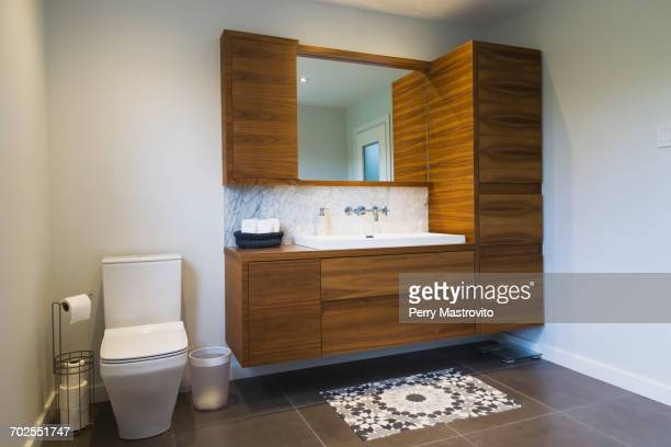 White high-back flush toilet and American walnut wood vanity with rectangular sink and ceramic tile flooring, Quebec, Canada