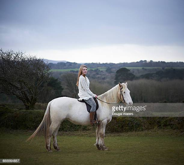 White horse and rider in countryside.