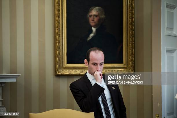 White House aid Stephen Miller listens while US President Donald Trump speaks to the press about an executive order on regulatory reform in the Oval...