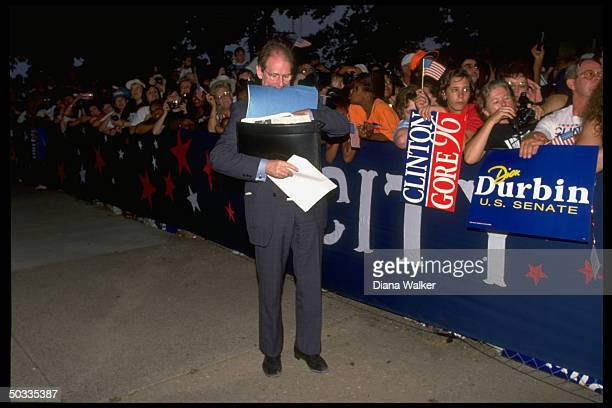 White House aide Harold Ickes juggling briefcase & papers, poised by ropeline in stop on Clinton campaign bus tour.