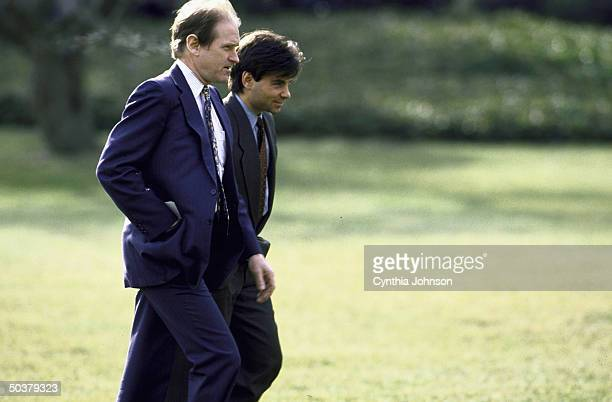 White House aides Harold Ickes & George Stephanopoulos walking on White House grounds.
