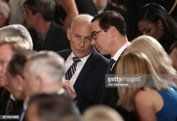 White House Chief of Staff Gen John Kelly confers with Treasury Secretary Steven Mnuchin while attending a ceremony where US President Donald Trump...