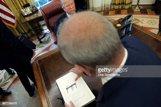 White House Chief of Staff John Kelly collects the tax reform bill from U.S. President Donald Trump's desk after he signed it in the Oval Office at...
