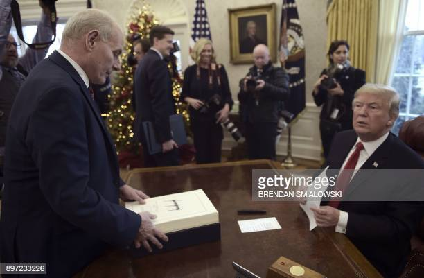 White House Chief of Staff John Kelly picks up documents off of United States President Donald J. Trump's desk during an event to sign the Tax Cut...
