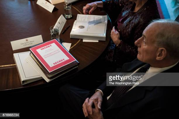 White House Chief of Staff John Kelly with papers marked secret in front of him listens as President Donald Trump announces that the United States...