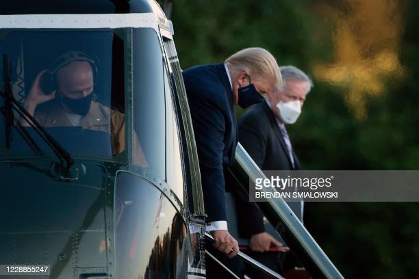White House Chief of Staff Mark Meadows watches as US President Donald Trump walks off Marine One while arriving at Walter Reed Medical Center in...