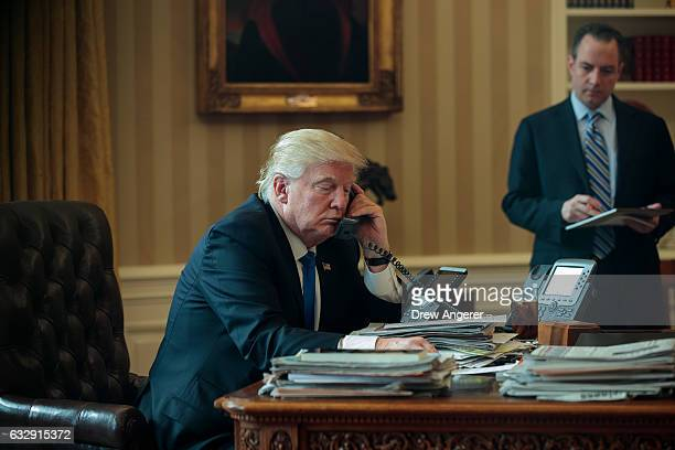 White House Chief of Staff Reince Priebus looks on as President Donald Trump speaks on the phone with Russian President Vladimir Putin in the Oval...