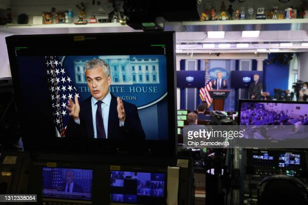 White House COVID-19 Response Coordinator Jeff Zients appears on a television screen while talking to reporters in the Brady Press Briefing Room at...
