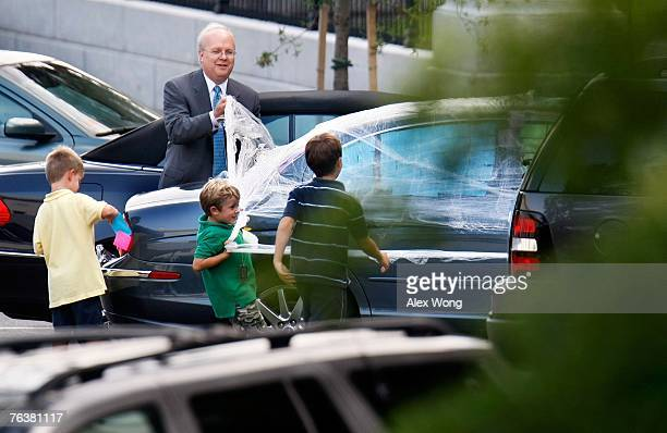 White House Deputy Chief of Staff Karl Rove with the help of some unidentified children remove plastic wrap on his vehicle set up by fellow White...
