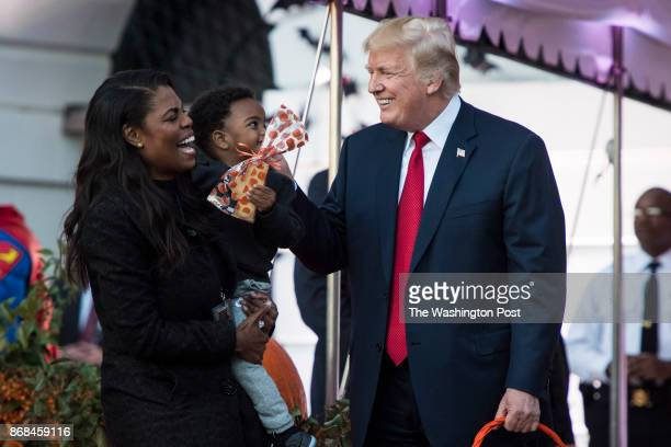 White House Director of communications for the Office of Public Liaison Omarosa Manigault talks with President Donald Trump as he hands out treats as...