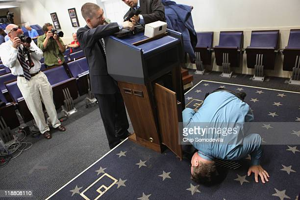 White House employees switch the regular Brady Press Briefing Room for the presidential podium in preparation for a news conference at the White...