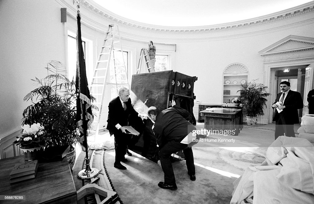 White House Head Usher Reex Scouten (L) supervises the removal of former President Bush's desk, at the stroke of noon, from the Oval Office January 20, 1993 in Washington, DC. It will be replaced by newly inaugurated President Clinton's desk, a desk which had previously belonged to President Kennedy.