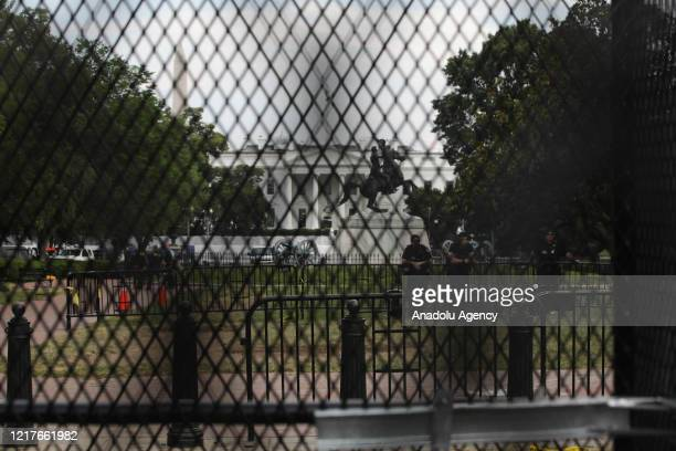 White House is seen behind a metal fence, built to keep protesters at bay at Lafayette Square during a protest over the death of George Floyd on June...