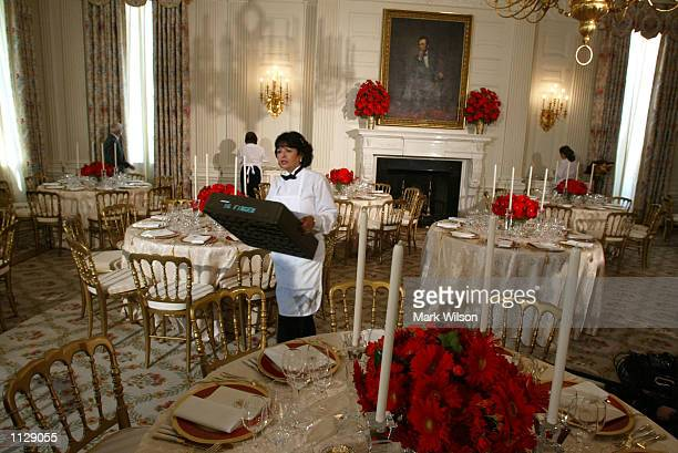 White House kitchen staff member prepares the State Dinning Room at the White House July 17, 2002 in Washington, DC. U.S President George W. Bush...