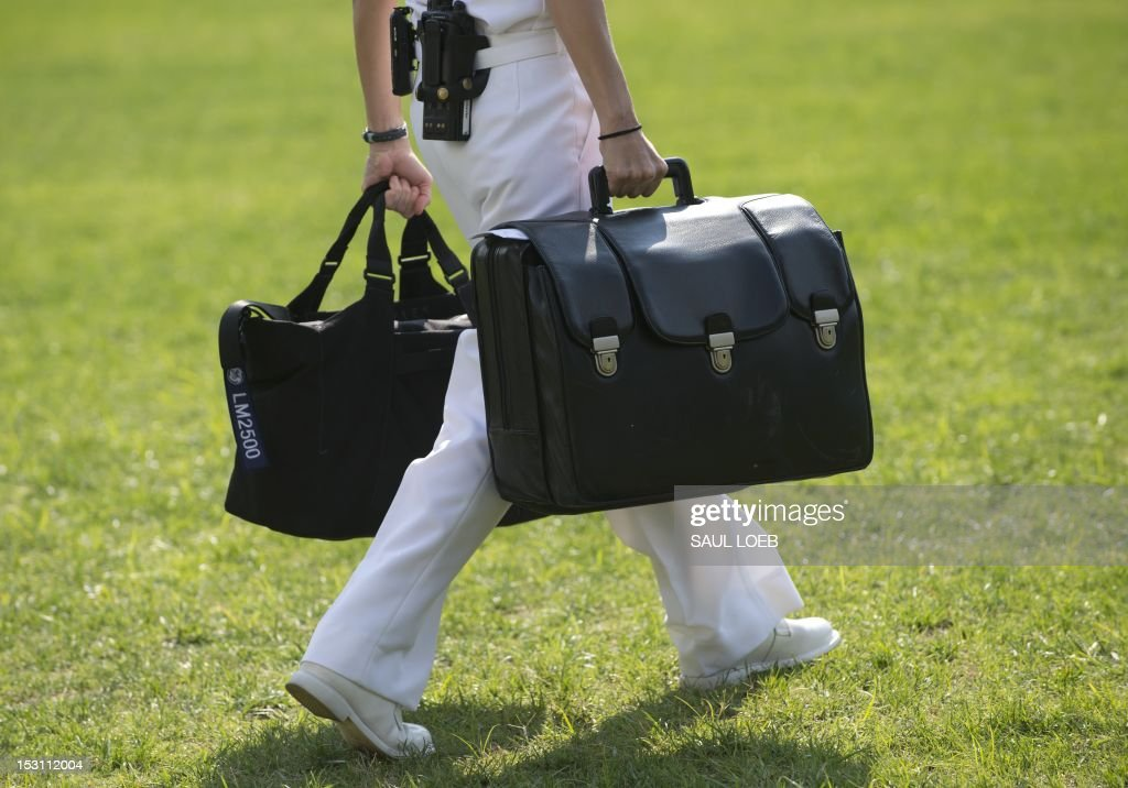 A White House military aide and member of the US Navy carries a briefcase known as the 'football,' containing emergency nuclear weapon codes, as US President Barack Obama departs on Marine One from the South Lawn of the White House in Washington, DC, September 30, 2012. AFP PHOTO / Saul LOEB