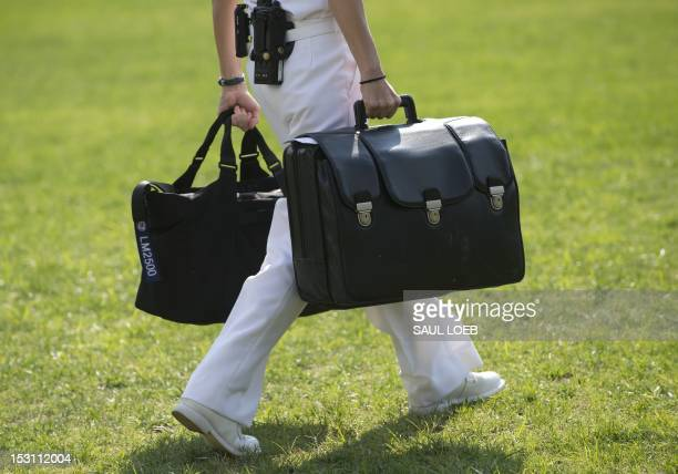 A White House military aide and member of the US Navy carries a briefcase known as the football containing emergency nuclear weapon codes as US...