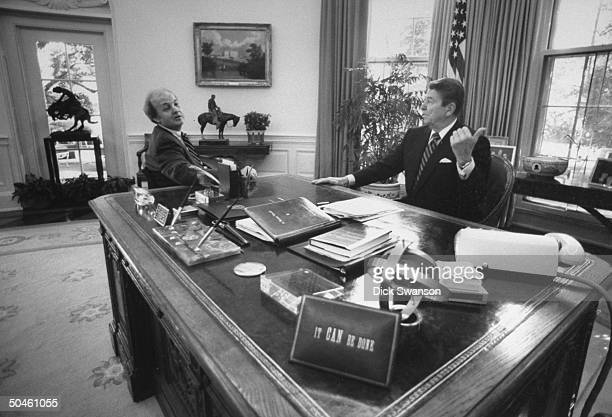 White House Press Secretary James Brady with President Ronald Reagan at Reagan's desk in the Oval Office