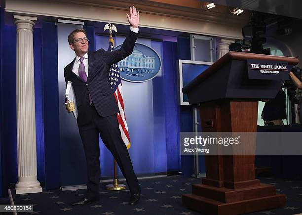 White House Press Secretary Jay Carney waves at the end of his last White House briefing at the James Brady Press Briefing Room of the White House...